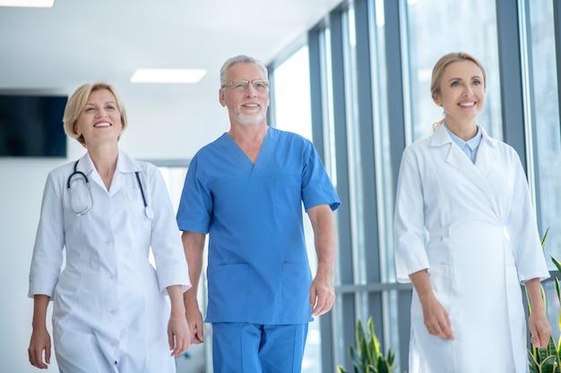 Meilleure équipe. groupe de travailleurs médicaux souriants marchant le long du couloir de l'hôpital