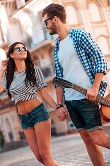 La meilleure journée. vue en contre-plongée d'un beau jeune couple d'amoureux se tenant la main et se regardant en marchant le long de la rue