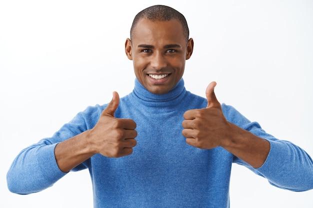 Meilleure offre en ligne. portrait d'un homme afro-américain confiant assurant son bon, montre le pouce levé comme recommande, approuve ou aime le produit