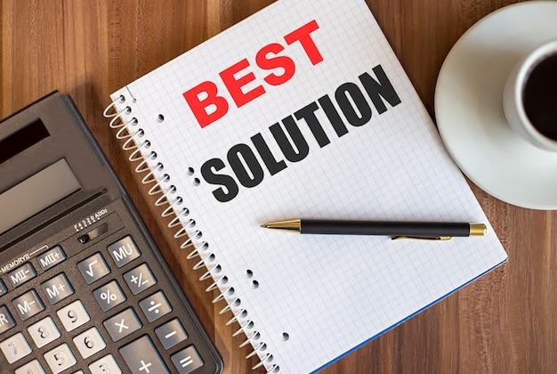 Meilleure solution écrite dans un bloc-notes blanc près d'une calculatrice et d'une tasse de café sur un fond en bois foncé