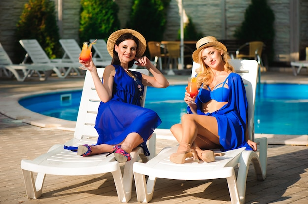 Les meilleures amies de la femme heureuse en vacances incroyables, boivent des cocktails près de la piscine et s'amusent