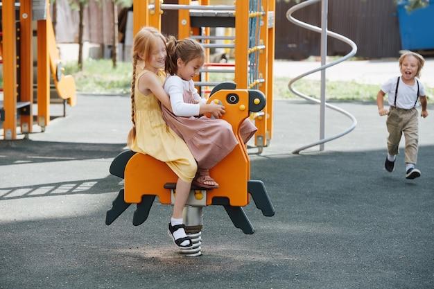 Meilleures petites amies jouant avec un cheval à ressort sur une aire de jeux pour enfants