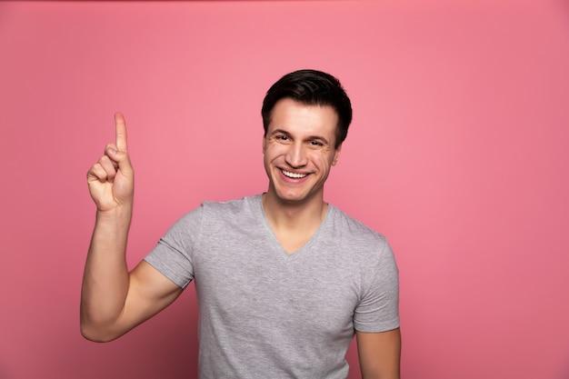 Meilleures ventes! beau jeune homme heureux dans un t-shirt gris, qui pointe vers le haut avec son index droit.
