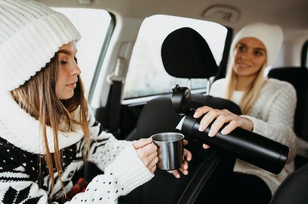 Meilleurs amis buvant du café dans la voiture