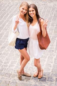 Meilleurs amis du monde. vue de dessus de deux belles jeunes femmes souriantes à la caméra et faisant des gestes tout en se tenant près l'une de l'autre à l'extérieur