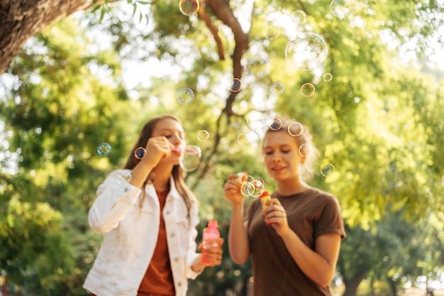 Meilleurs amis faisant des bulles de savon à l'extérieur