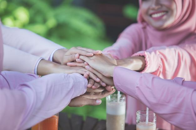 Meilleurs amis femme mettant les mains ensemble au café