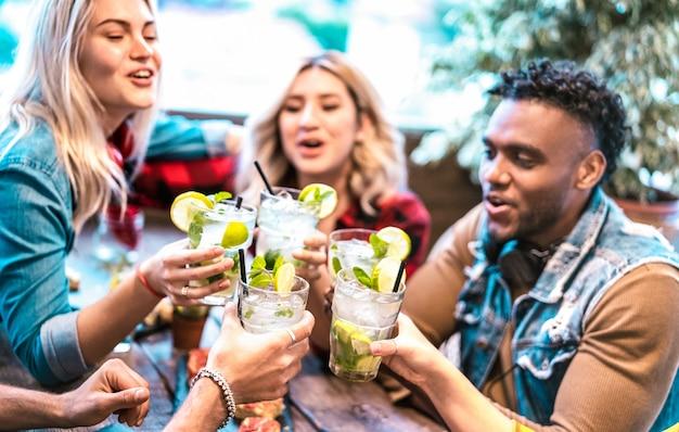 Meilleurs amis grillant des boissons mojito au restaurant bar à cocktails fashion