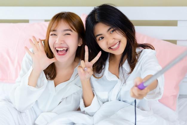 Meilleurs amis joyeux avec selfie sur le lit