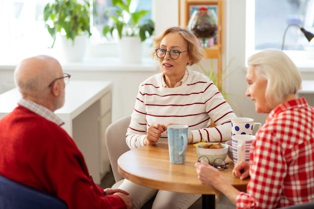 Meilleurs amis. des personnes âgées agréables qui se parlent tout en buvant un délicieux thé ensemble