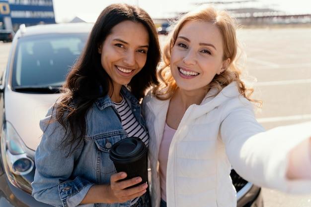 Meilleurs amis prenant un selfie avec leur voiture