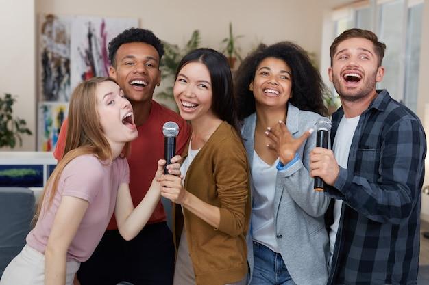 Meilleurs amis s'amusant groupe de jeunes amis multiculturels heureux chantant avec microphone ensemble
