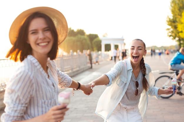 Les meilleurs amis se tenant la main et rire