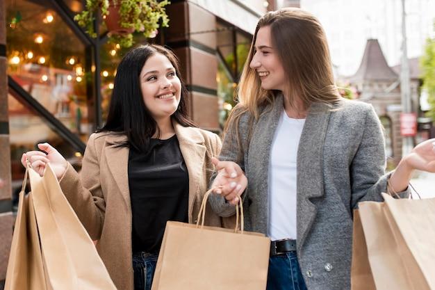 Meilleurs amis tenant des sacs à provisions à l'extérieur