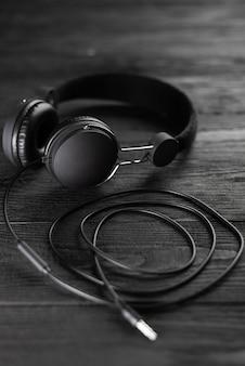 Meilleurs écouteurs pour la musique. les écouteurs sont de couleur sombre contre un mur en bois. écouteurs pour la production musicale.