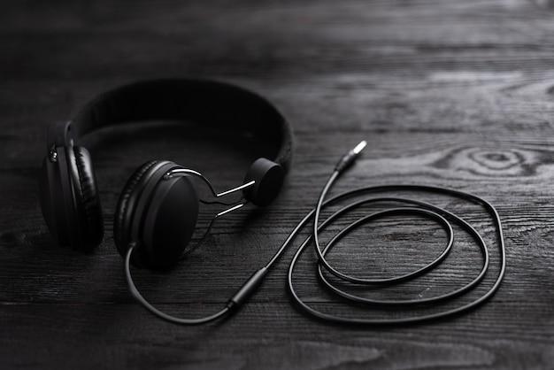 Meilleurs écouteurs pour la musique. les écouteurs sont de couleur sombre contre un mur en bois.