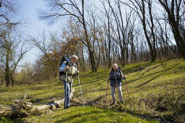 Meilleurs moments ensemble. couple de famille âgés d'homme et de femme en tenue de touriste marchant sur la pelouse verte en journée ensoleillée près du ruisseau. concept de tourisme, mode de vie sain, détente et convivialité.