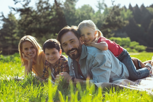 Les meilleurs parents de tous les temps. joyeux papa barbu souriant et allongé sur la couverture avec sa famille