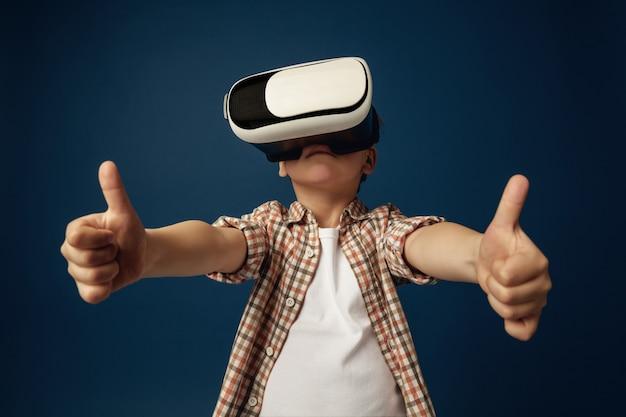 Meilleurs souvenirs. petit garçon ou enfant en jeans et chemise avec des lunettes de casque de réalité virtuelle isolés sur fond bleu studio. concept de technologie de pointe, jeux vidéo, innovation.