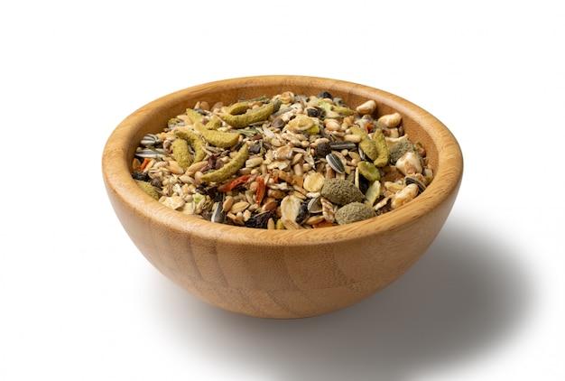 Mélange d'aliments secs pour rongeurs pour souris, lapin ou degu dans un bol en bois isolé sur fond blanc avec un tracé de détourage.