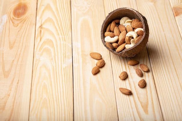 Mélange d'amandes, noix de cajou dans un bol de noix de coco sur l'espace de copie de table en bois. source de protéines végétaliennes
