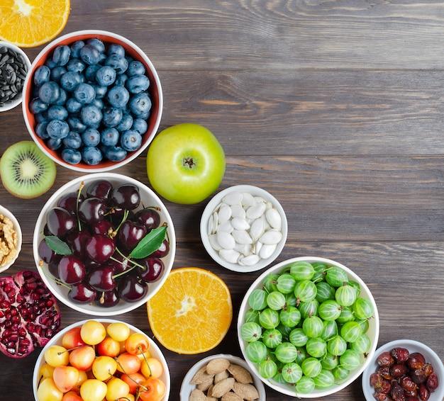 Mélange de baies fraîches, de noix et de fruits. une alimentation saine contient beaucoup de vitamines et d'oligo-éléments utiles.fond en bois brun. copiez l'espace.
