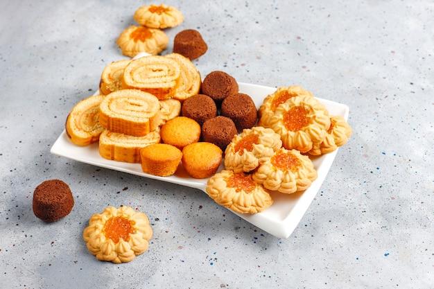 Mélange de biscuits sucrés, cake roll, mini cupcakes.