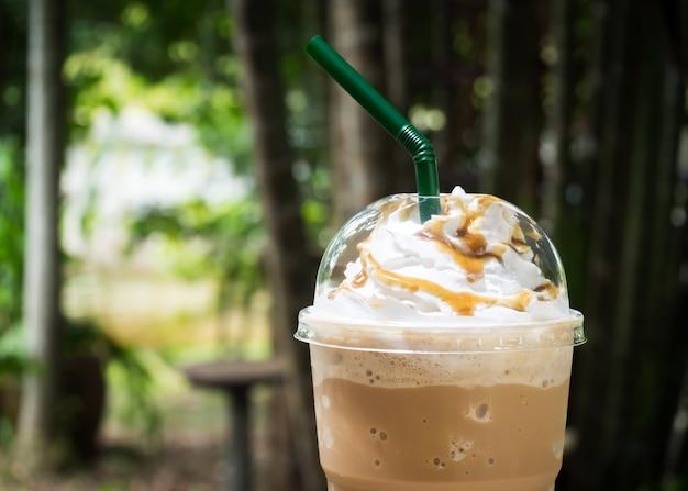Mélange de café dans une tasse en plastique. servi avec une garniture de crème fouettée et un sirop sucré.
