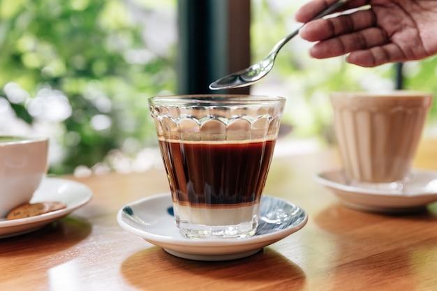 Mélange de café noir avec du lait concentré en verre transparent