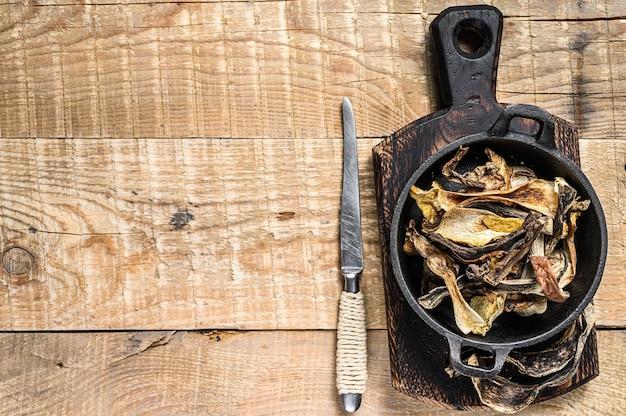 Mélange de champignons sauvages séchés hachés dans une casserole. fond en bois. vue de dessus. espace de copie.