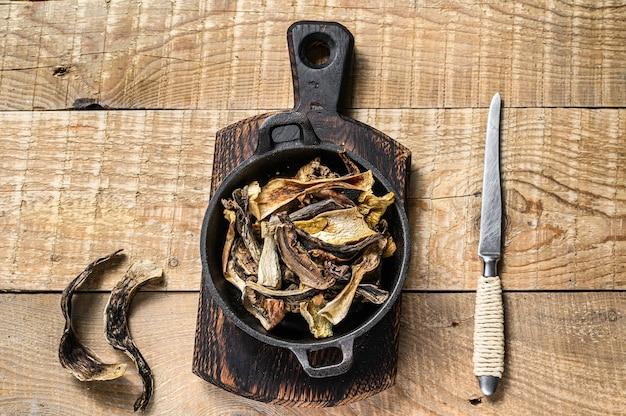 Mélange de champignons sauvages séchés hachés dans une casserole. fond en bois. vue de dessus.