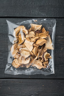 Mélange de champignons séchés sauvages hachés, ensemble sur fond de table en bois noir, en emballage plastique, vue de dessus à plat
