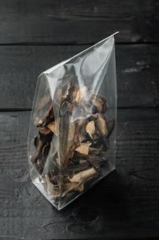 Mélange de champignons séchés sauvages hachés, ensemble sur fond de table en bois noir, en emballage plastique
