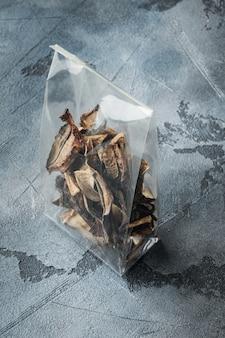 Mélange de champignons séchés sauvages hachés, sur fond gris, dans un emballage en plastique