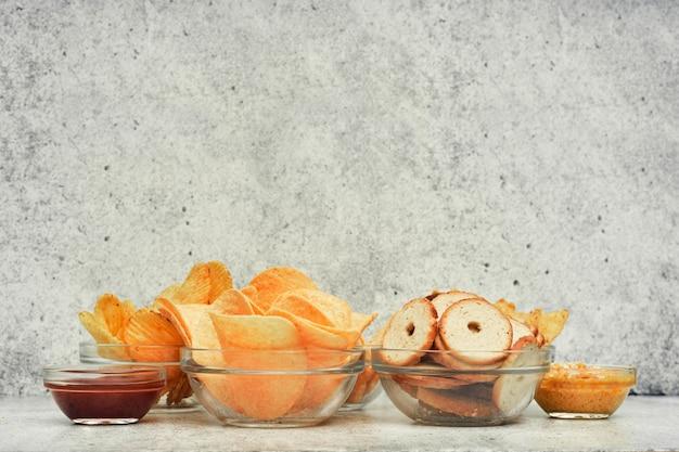 Mélange de chips, collations et craquelins sur un support en bois. nourriture malsaine, collation de bière, repas prêt. fermer