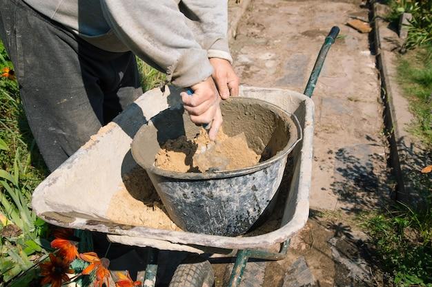 Mélange de ciment pour remplir l'allée du jardin, travaux de construction de jardin.