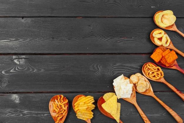 Mélange de collations: bretzels, craquelins, chips et nachos sur le fond de la table