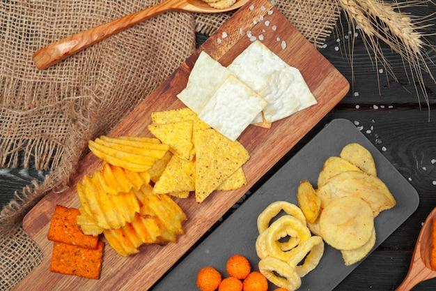 Mélange de collations: bretzels, craquelins, chips et nachos sur la table