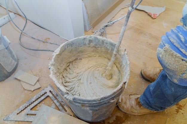 Mélange de colle à carrelage ou de ciment avec une perceuse électrique