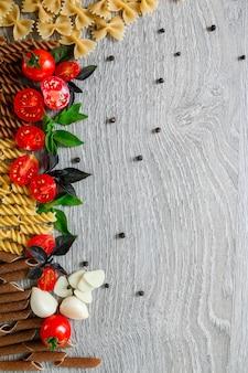 Mélange de deux pâtes colorées près de tomates, ail et basilic sur fond de bois gris. cadre de pâtes crues. copiez l'espace. mise à plat.