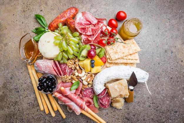 Mélange de différentes collations et apéritifs. tapas espagnoles ou vin italien sur une assiette en bois