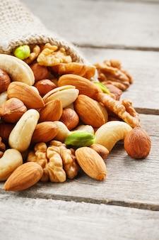 Mélange de différentes noix dans une tasse en bois contre le tissu de jute. les noix comme structure et fond, macro. vue de dessus.