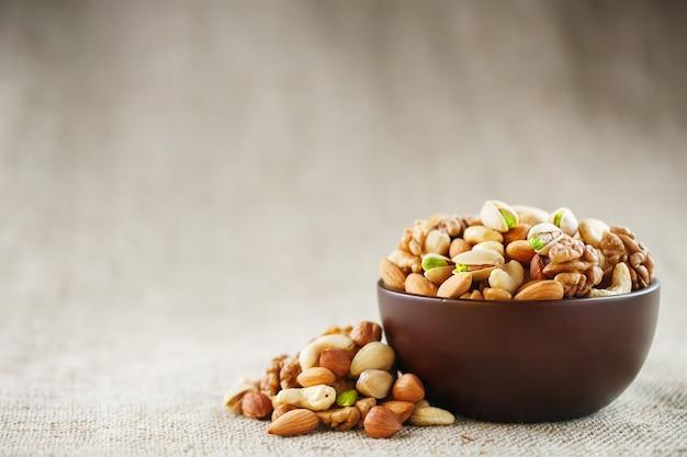 Mélange de différentes noix dans une tasse en bois sur fond de toile de jute