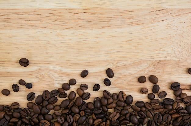 Mélange de différentes sortes de grains de café sur fond en bois. fond de café
