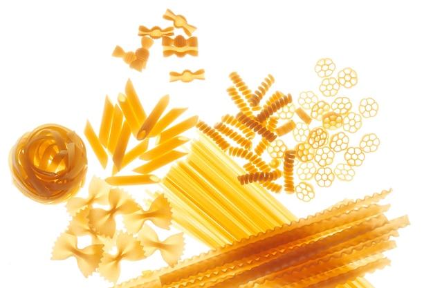 Mélange de différentes variétés de pâtes sur une surface blanche, éclairage inférieur, assortiment de macaronis