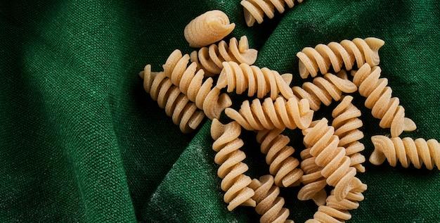 Mélange de différentes variétés de pâtes sur une surface en tissu vert, cuisson concept de macaronis assortis