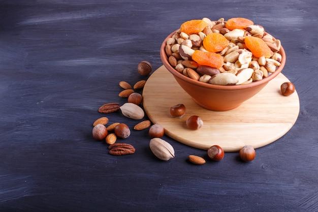 Mélange de différents types de noix dans un bol en céramique sur un fond en bois noir avec espace de copie.