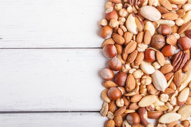 Mélange de différents types de noix sur un fond en bois blanc avec espace de copie.