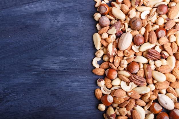 Mélange de différents types de noix sur un fond en bois noir avec espace de copie.