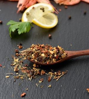 Mélange de diverses épices séchées dans une cuillère en bois brun, fond noir, gros plan